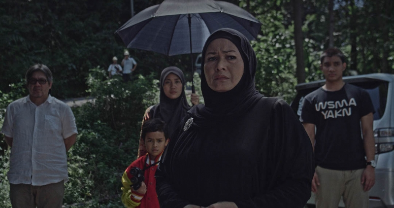 A group of people including two women in hijabs, medium skin tone, in a public park looking towards the camera with worry.