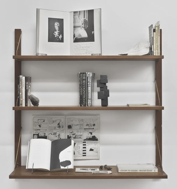 A sculptural installation of books, a bronze sculpture, a rock, and other objects displayed on three wooden shelves.