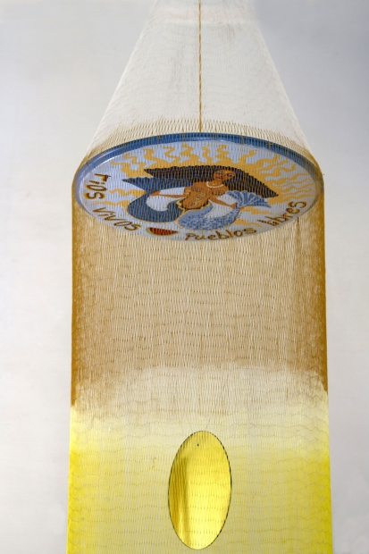 A form that looks like a mobile or a fishing net with orange and yellow fibers hangs suspended. At the bottom, small objects hang from strings in a corkscrew shape.