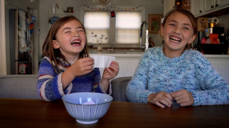 Two children smiling and sitting at the dining table in their home, with one holding up a piece of paper drawn from a ceramic bowl.
