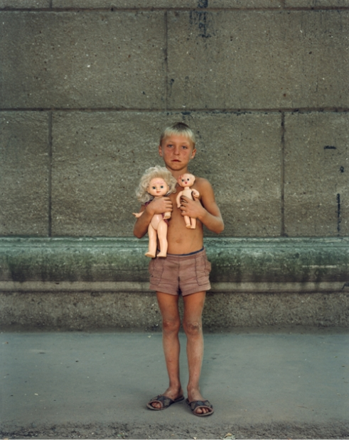 A color photograph of a tanned and dirty young boy with blond hair wearing only shorts and  clutching two unclothed dolls against his bare chest.