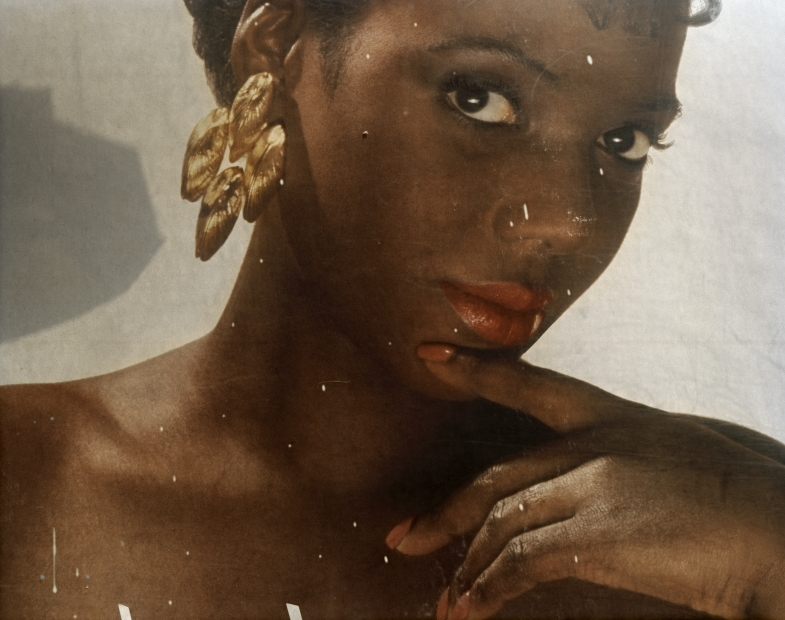 Scratched up reproduction of a vintage-looking photo of a woman with dark skin, gold hanging earrings, and matching coral lips and nails looking at the camera from a slight angle