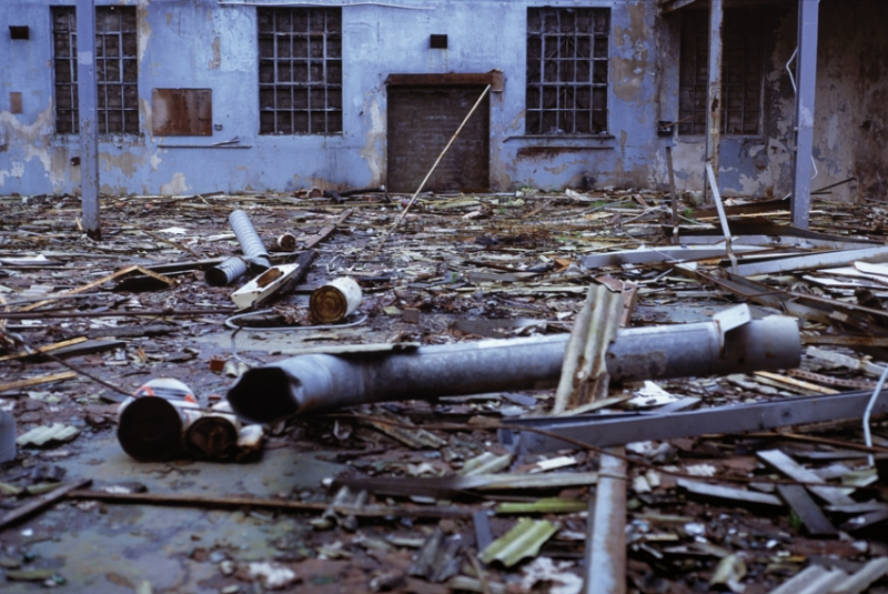 A color photograph of an industrial yard covered in debris with a dilapidated building in the background.
