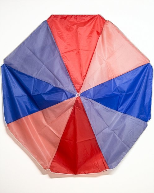 A sculpture composed of red and blue fabric panels removed from an umbrella, some bright and some faded.