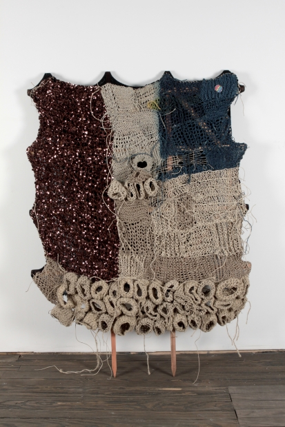 A textile sculpture composed of woven, sewn, and crocheted fibers stretched on a wooden garden trellis leaning against a wall.