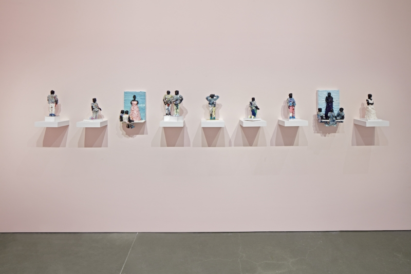A pale pink wall features 9 small figures made out of paint sitting on small white wall-mounted pedestals.