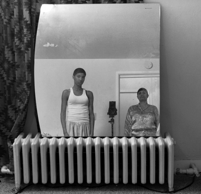 A black-and-white photograph shows the artist, a Black woman, and her mother in lounge wear and hair caps reflected in a mirror resting on a gas radiator.