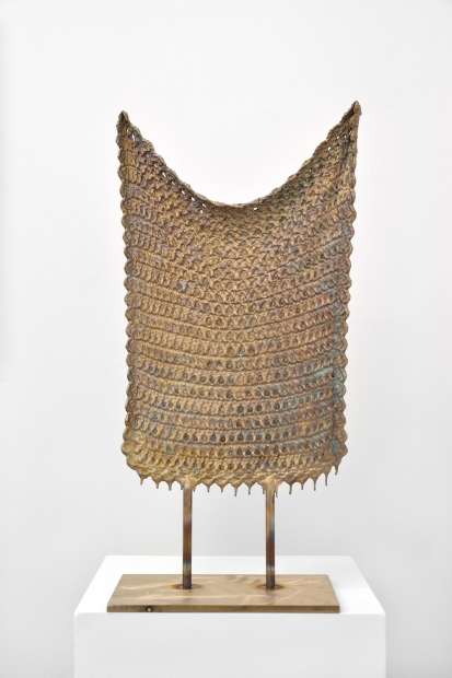 A bronze sculpture of a knitted blanket suspended between two rods on a narrow metal plinth.