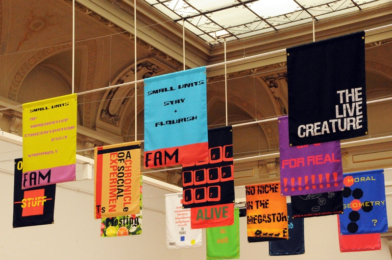Installation of brightly printed banners with text hanging in rows along the ceiling