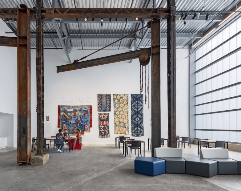 """A room with white walls, iron beams and gantries, a selection of colorful fabric wall hangings under the title """"INDIGO,"""" and three people sitting at a small table."""