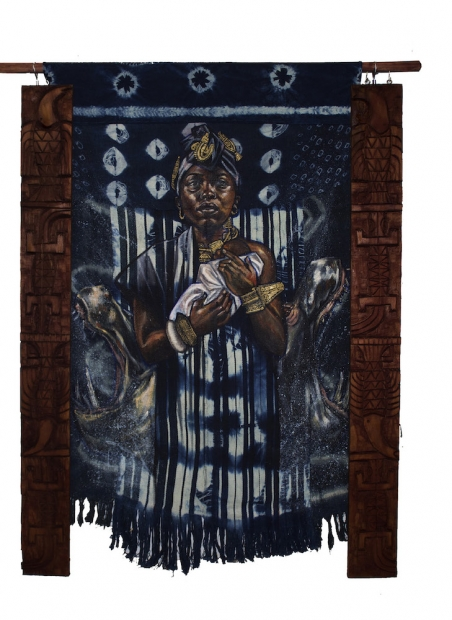 A painting on indigo-dyed fabric depicts a woman holding an infant as she looks directly at the viewer. It is flanked by carved wooden pieces.