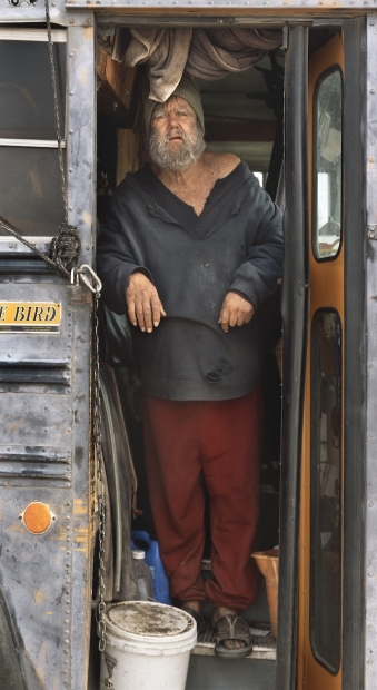 A color photograph depicts a full portrait of a light-skinned man in dirty, ragged clothing standing in the open doors of a school bus as he looks directly at the viewer.