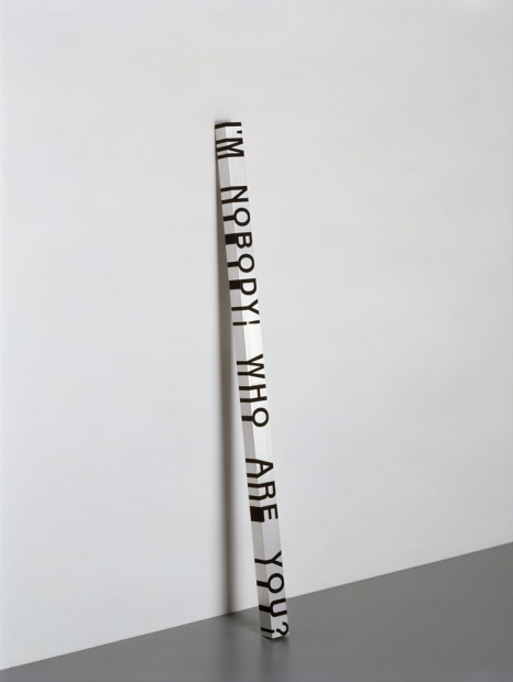 "A sculpture depicts a rectangular white pole leaning against a white wall with black text reading, ""I'm nobody! Who are you?"" vertically down one side."