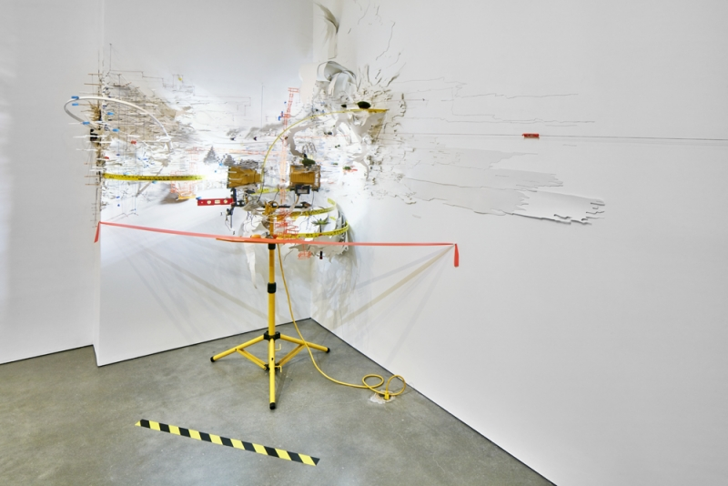 An elaborate mixed media installation occupying the corner of a white room and consisting of peeling white material, various yellow and orange materials, and a yellow metal tripod.
