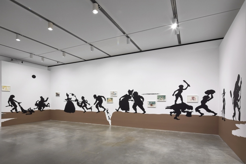 A photograph of an installation comprising black, life-size silhouettes on a brown ground acting out a series of scenes across three walls of a gallery.