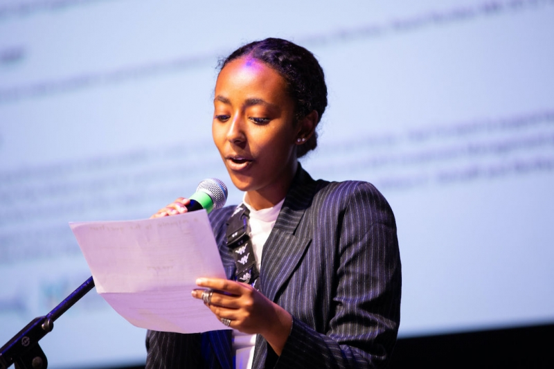 A medium-dark skinned young person speaks into a mic while reading off a paper with a monitor projection behind them.