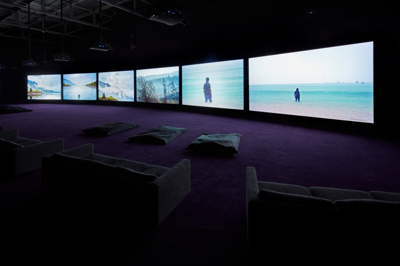 An installation photograph depicts a dark purple-carpeted viewing room with six large screens showing scenes of water and shorelines.