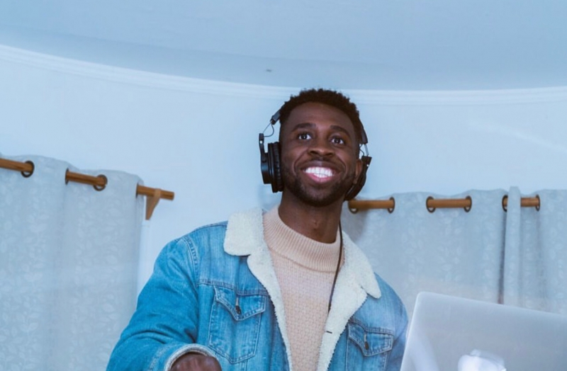 DJ SUNRAE smiling and wearing headphones .