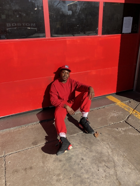 A man wearing all red sitting on a pavement against a red-colored building.