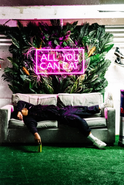 A person laying on a couch under a neon sign reading ALL YOU CAN EAT.