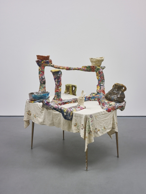 A sculpture consisting of a colorful ceramic and papier mache structure with multiple arms holding ceramic vessels and displayed on a table with an embroidered white tablecloth.