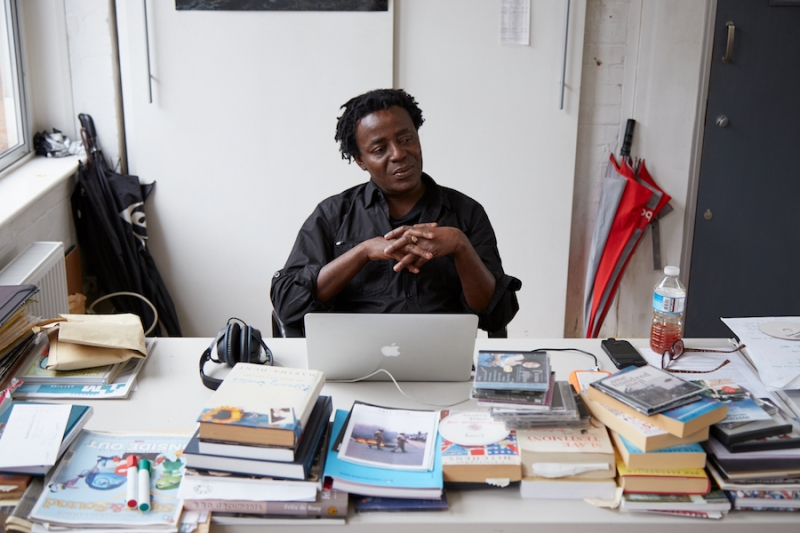 British-Ghanian artist John Akomfrah sits with folded hands behind a white desk stacked with books and CDs. He looks down and to his left and is wearing a black button-up-shirt with the sleeves pushed up.