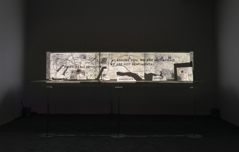 "A wide-screen projection in a dark room of a black and white collage encompassing maps and the texts ""bring me my resolve"" and ""I assure you we are not afraid. We are not sentimental."""