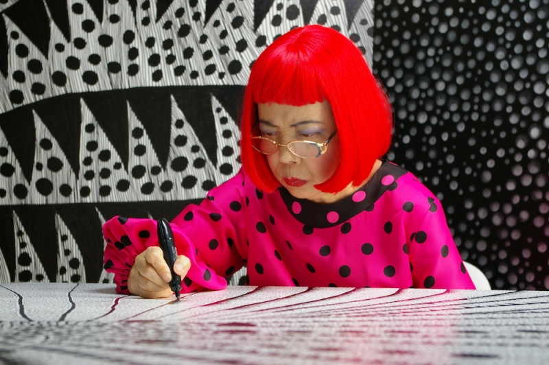 The artist Yayoi Kusama works on a large black and white drawing covering a table with a black magic marker. Behind her is a wall of black and white patterns featuring dots. She is wearing a bright red pageboy wig and a magenta dress with black dots.