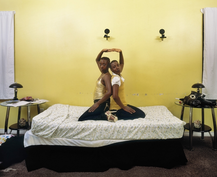 In this photo two adolescent girls kneel back to back on an unmade bed, looking at the camera. They are wearing black pants and gold tops and each have one arm stretched up and touching the other's hand. The wall behind them is yellow with scuff marks. The sheets are white with yellow flowers.