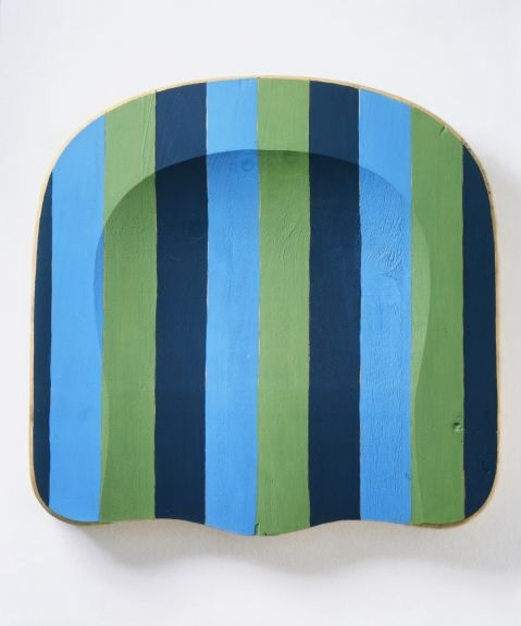 The seat of a wooden chair painted in navy, blue, and green vertical stripes and hung vertically on a wall.