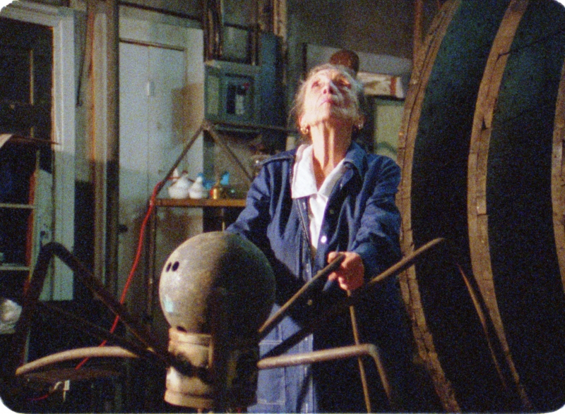 Inside an industrial studio, an elderly white woman looks up as she holds onto spider legs-like pipes from a metal sculpture.