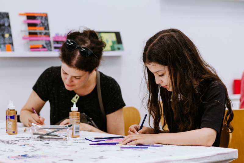 A parent and child concentrating and looking down while making art during an ICA Play Date.
