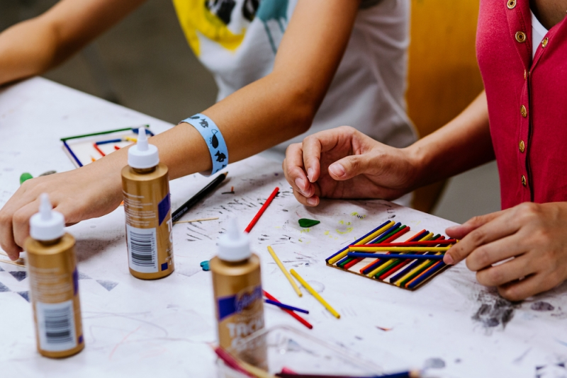 A close-up image of two pair of hands with colorful pencils and glue on an art-making table.