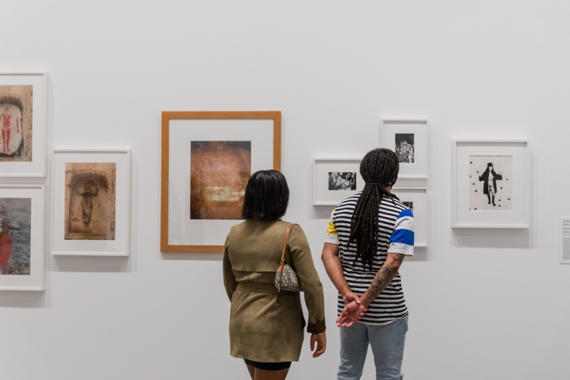 Two visitors from behind viewing framed photographs on the gallery wall.