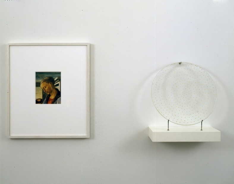 "An installation of two objects hung side by side a framed reproduction of Sandro Botticelli's ""Virgin and Child with an Angel"" oil painting and a circular glass plate speckled in gold stars that casts a halo shadow on the wall."
