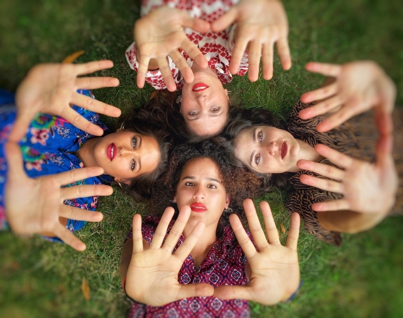 Seen from above, four young women lay in grass with their heads together and their hands extended toward the camera.
