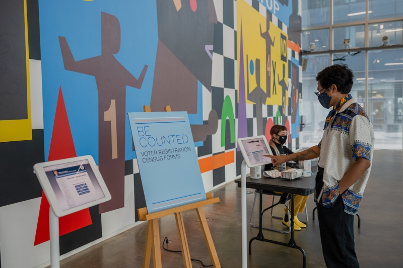 """In front of ICA's art wall, a medium dark-skinned man points to an iPad device on a stand and a sign that reads """"Be Counted"""" sits on an easel display."""