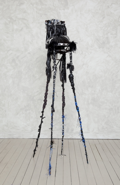 A sculpture comprised of a black wooden chair with elongated, spider-like legs that towers in height and is decorated with black feathers, black and silver tinsel, and hair.