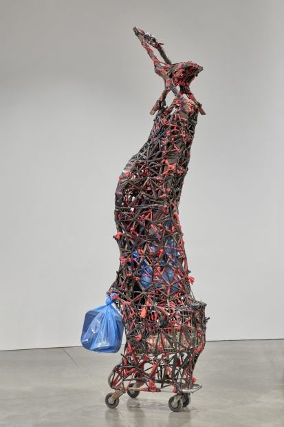 A sculpture made of various objects piled on top of a metal shopping cart, tightly wrapped and bound with twisted red and black plastic, culminating in a simple folding chair at the very top.