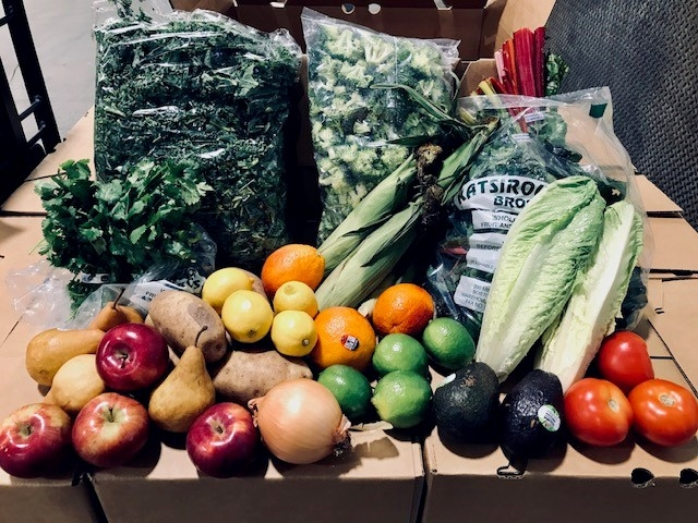 Fresh fruit and vegetable produce on top of shipping boxes.