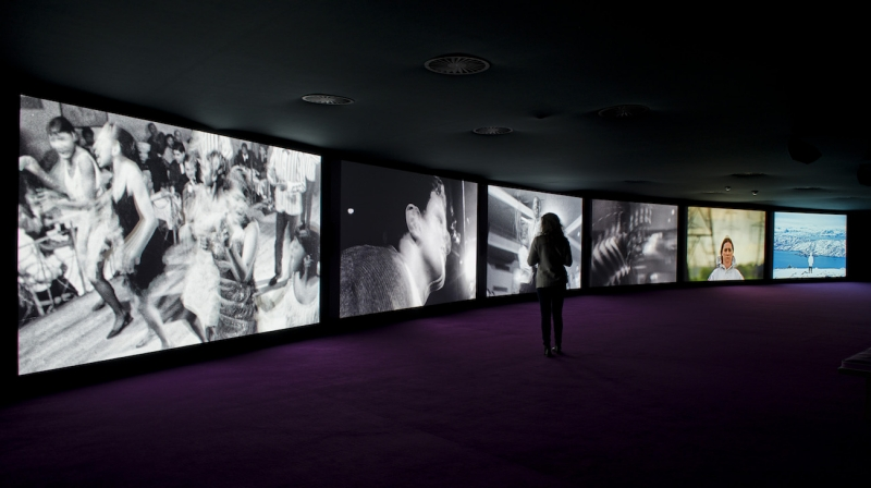 Six large video screens arranged side by side in a gentle curve fill a dark room. A woman stands before them, watching. They each display a different image, some black and white, including people dancing, some color.