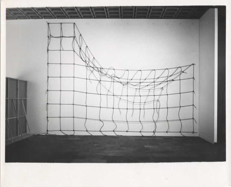 A black-and-white photograph of an installation of brown rope knotted in a grid and hung on a white gallery wall, with the top right corner detached and hanging down.