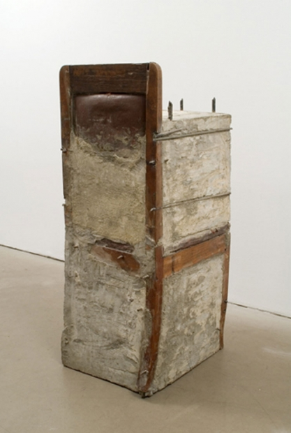 A sculpture consisting of a wooden chair almost completely within an unfinished block of cement and rebar.