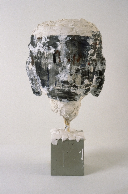 A sculpture of an abstracted, figurative head comprised of mixed materials and suspended upright on a display plinth.