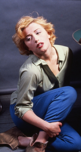 A color photograph of artist Cindy Sherman, a white woman, posed as Marilyn Monroe with blond hair and parted red lips, seated on the floor in jeans, boots, and a pale blouse.