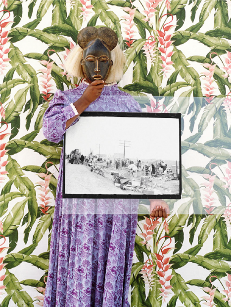A color photograph of a Black woman in a full-length purple patterned dress, standing in front of floral wallpaper and holding a West African mask over her face and a large vintage black-and-white photograph.