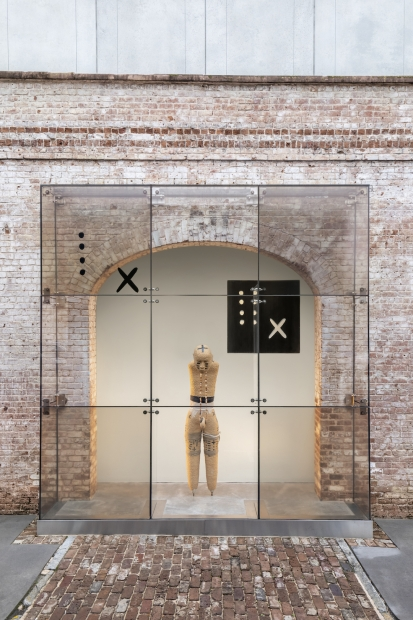 A mannequin without arms or feet sticks its head out forward, tilted downward. The figure is painted with designs and adorned with a necklace and is encased in a tall clear case made of see-through square panes. The  figure stands in a large brick archway, with a brick pathway leading to the clear case.