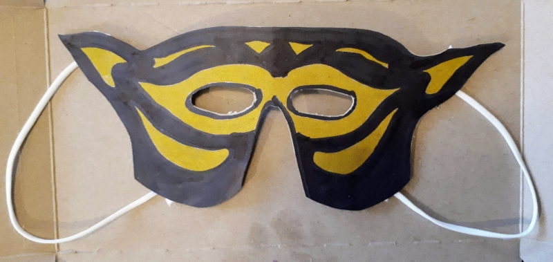 A black and yellow costume mask made from paper