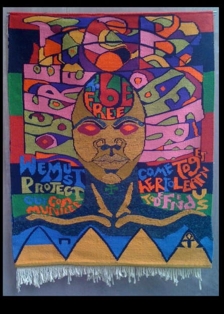 """A colorful textile depicting a face with brown skin and red eyes surrounded by words including """"To be free."""""""