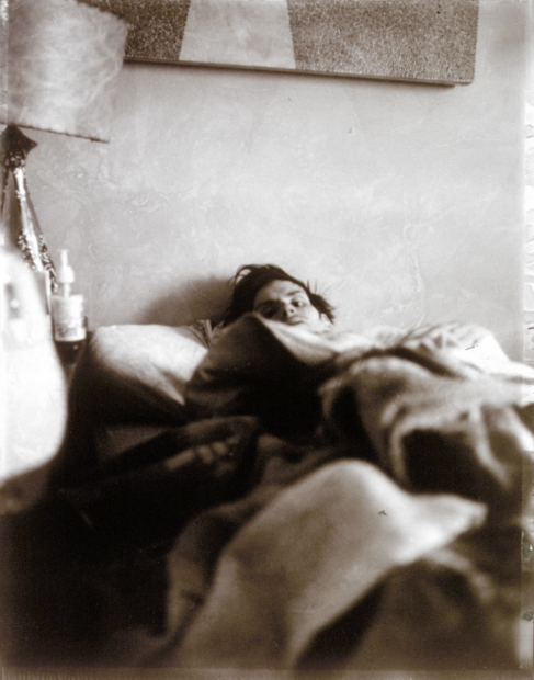 A black and white photograph shows a man under covers in bed. The photograph appears to be shot from near his feet. We see the bottom part of an artwork on the wall behind the bed and a lamp at left.